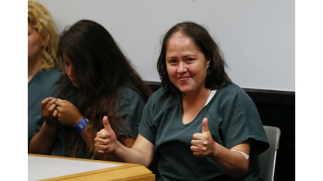 Woman charged with killing family smiles in court, gives thumbs up